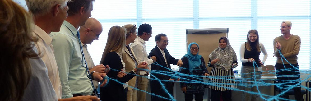 A diverse group of smiling people hold entwined strands of blue wool as part of a learning exercise