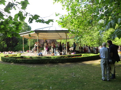 People dancing in a bandstand in a green leafy park