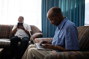 senior-man-using-laptop-while-sitting-on