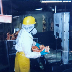 Boning room employee cutting loins at the band saw station, 1999