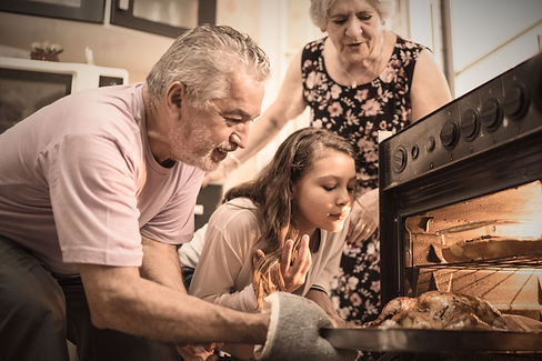 Grandparents cooking with their granddaughter