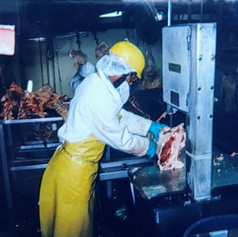Boning room employee cutting loins at the band saw station, Lee Meats, 1999