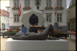 vendor in front of recling sculpture