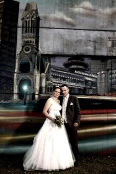 Ist es die echte? Nein, dieses Brautpaar steht vor einem Wandbild der Gedächtniskirche in Berlin-Charlottenburg.