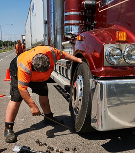 Emergency roadside service member replacing truck tyre