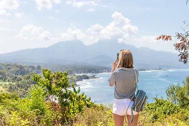 Pexels Woman taking photo enjoying view.