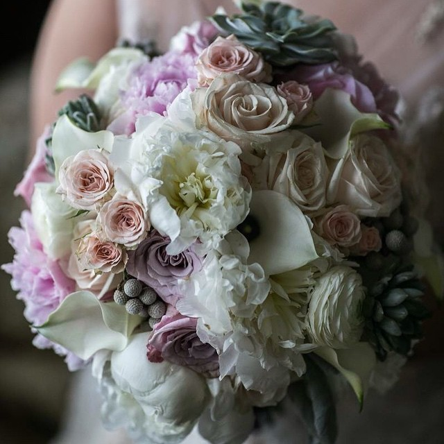 Lush hand-tied bouquet featuring a full display of peonies, garden roses, calla lilies, roses and su