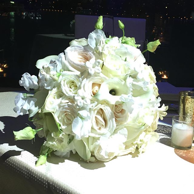 Beautiful all-white bouquet of roses, garden roses, calla lilies, lysianthus, ranunculus and sweet p