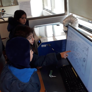 Students check their design before they begin printing on the laser cutter.