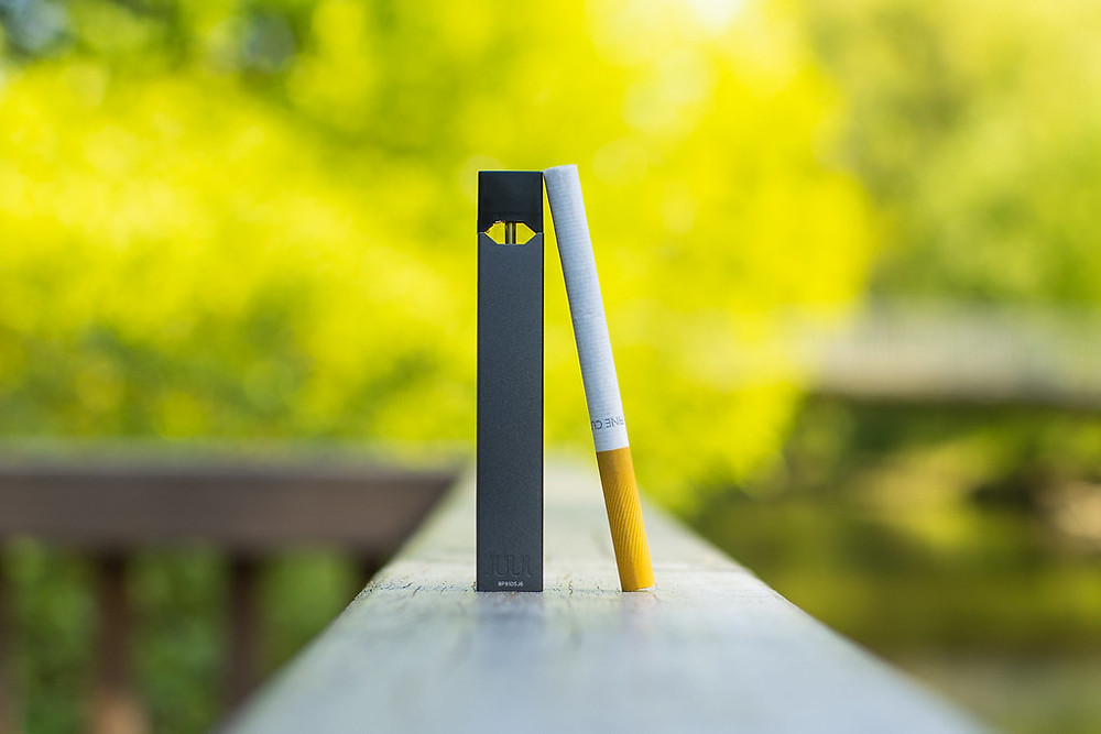 Photograph of a Juul and a Cigarette