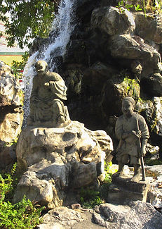 Waterfall with statues on rocks in front at Wat Pho, Thailand