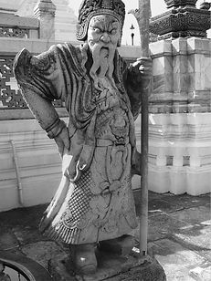 Black and White Pic of Thai Guard Statue holding a staff at the Grand Palace