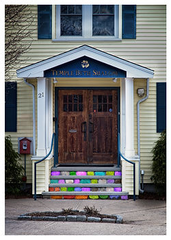 A color photography of the entrace to a Jewish Temple that has the stone steps painted in the color of various pride flags.