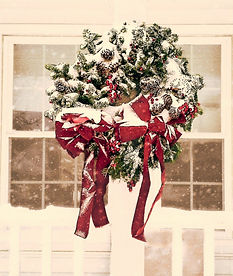 A Norman Rockwell-esk photo of a Christmas Wreath with pinecones and a red ribbon dusted with snow hanging in front of a window as snow falls.