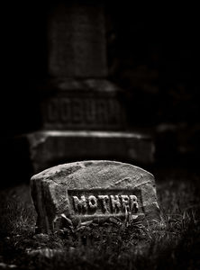 """A Black & White image of an old tombstone that has the generic inscription of """"mother"""" on it with a larger monument tombstone in the background"""