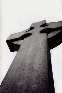 A black and white photo of a celtic cross looking up from base to top.
