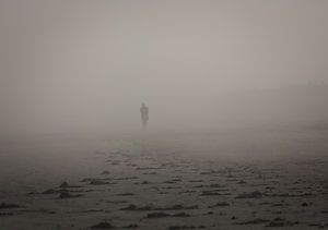 A color (NOT black and white) image of the silouhette of a man walking through the fog on a beach with footprints in the sand in the foreground.