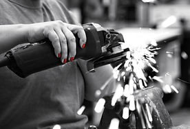 Black and white pic of a woman grinding steel white, with red fingernails.