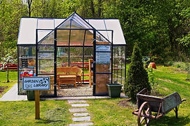 A picture of a green house turned into a mini library in a field with garden equipment around it.