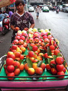 Thai Fruit Vendor selling apples from a cart on the street