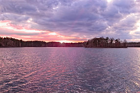 A photo of a lake and island at susnet with dramatic pink, blue, and purple clouds and dark, rippling water.