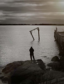 A Black and White/Color imgae of a man in silhouette standing on a rocky shore fishing into a bay with the sun flaring onto the water and an abandoned dock.