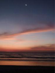 Thai Beach Moonrise at sunset over the ocean