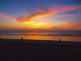 Two people walking on a beach at Sunset in California