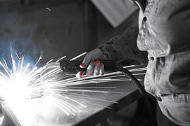 Black and white pic of a woman welding steel with red fingernails.