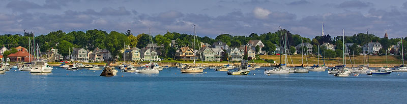 A panoramic shot of boats in a bay of blue water with houses and trees behind on a sunny day in Salem, Massachusetts.