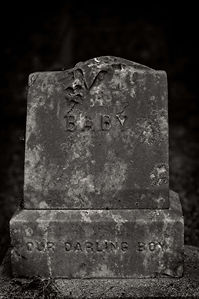 """A Black & White image of an old tombstone that says """"Baby, Our Darling Boy"""" with an old design on the top."""