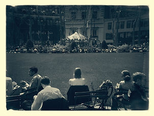 Black and White pic of a woman in a park watching a carousel.