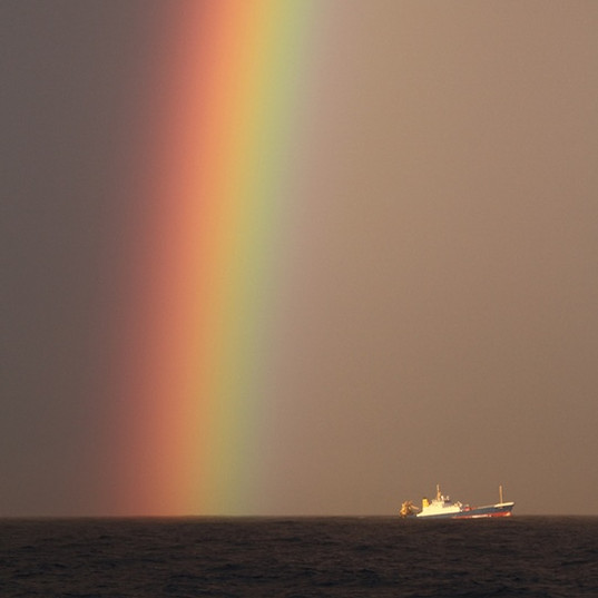 Rainbow and fishing boat