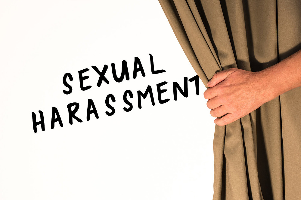 Image with the words sexual harassment revealed from behind a curtain
