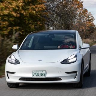 White Tesla Model 3 driving down a street