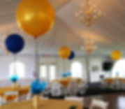 For a company's milestone, three foot balloons were placed in gold vases at each table!