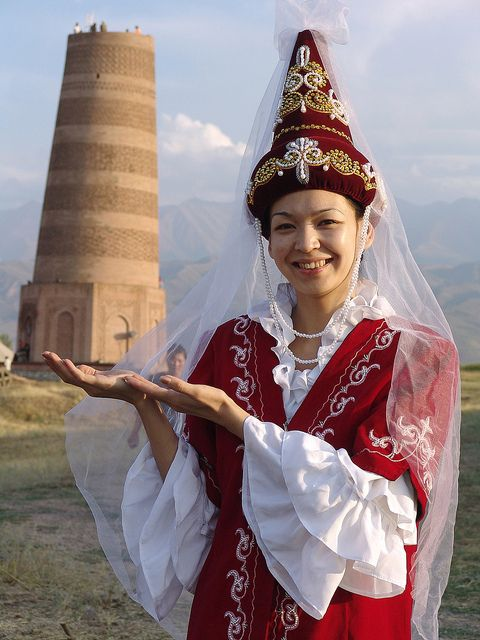 A Kyrgyz woman standing in front of one of Kyrgyz's largest minarets wearing traditional Kyrgyz garb
