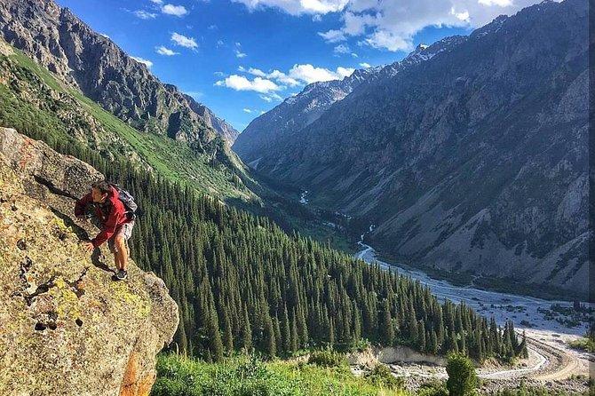 A hiker climbing the side of a steep mountain inside the Ala Archa National Park