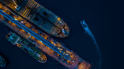 Aerial view oil tanker ship at the port at night, import export business logistic and transportation