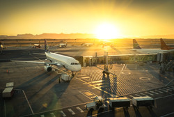 Airplane at the terminal gate ready for takeoff - Modern international airport during sunset - Conce