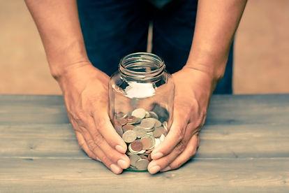 man-holding-glass-jar-that-are-money-sav