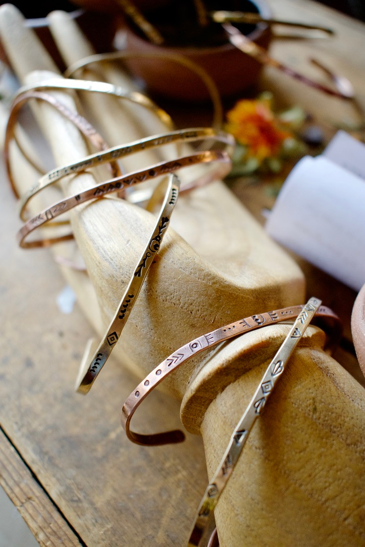 Handcrafted & individually stamped Copper and Brass bangle bracelets by Christina Holland Designs. Photo by Weston Holland Photography.