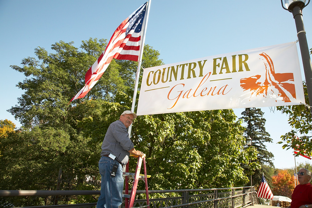 Ron Smith hanging a banner at the park entrance.