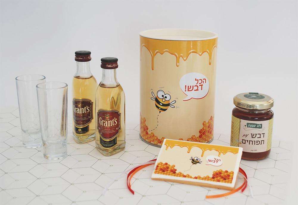 הכל דבש: מארז ממותג לראש השנה הכולל: צנצנת דבש, בקבוקי אלכוהול, כוסות צ'יסר וברכה על עוגיה מעוצבת