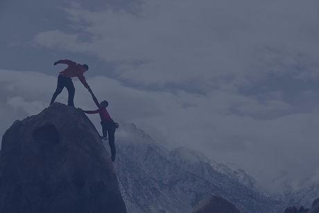 Ein Bild mit zwei Bergsteigern wobei einer bereits am Gipfel steht und dem anderen die Hand reicht um ihn auf den Gipfel zu ziehen.
