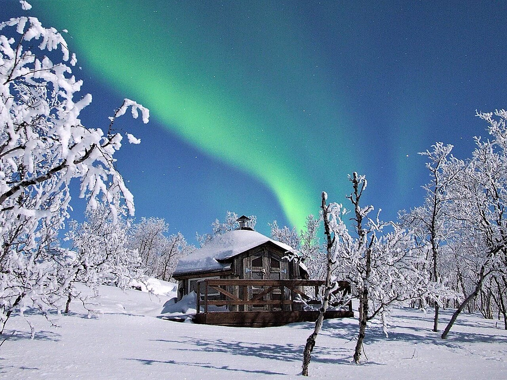 A small wooden hut surrounded by frozen trees and snow. A moonlit blue sky with stars and a broad, bright green streak of aurora borealis (Northern Lights).