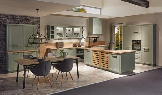 Cuisine façades vert avec un plan de travail bois