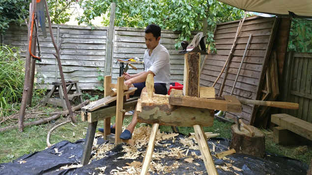 client using shave horse to round legs of a stool