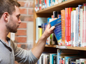 Area Man Debates Which Book To Lie Unread on Nightstand For January