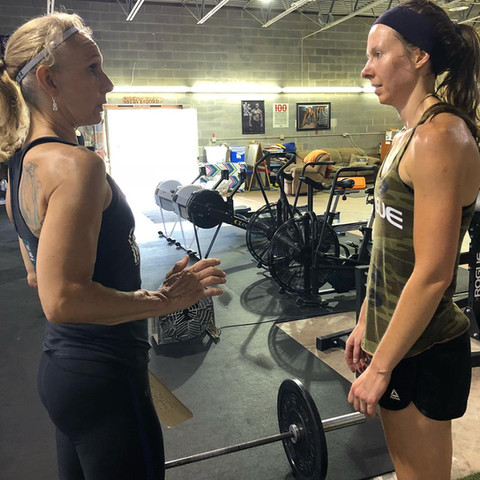 Coach Lona instructing Misfit athlete, Lizz Herman, on a movement during a Saturday morning Partner WOD.
